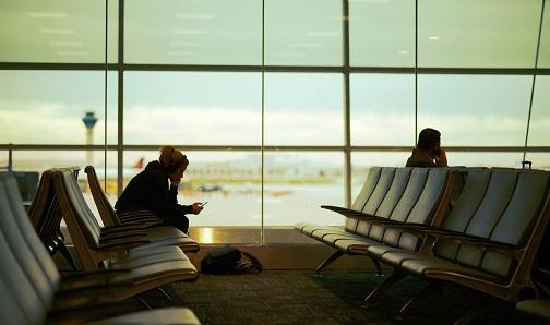 reizigers op luchthaven die een Schiphol taxi bestellen