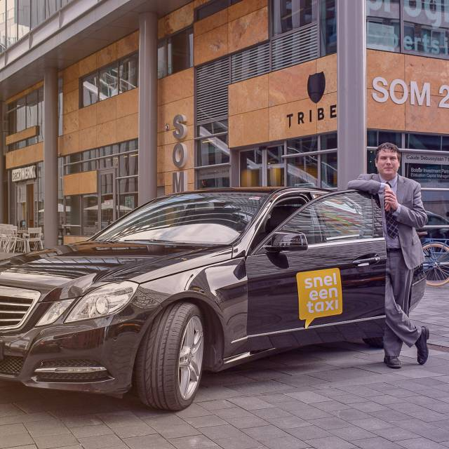 Een vervoerder van taxicentrale Rotterdam staand naast zijn taxi